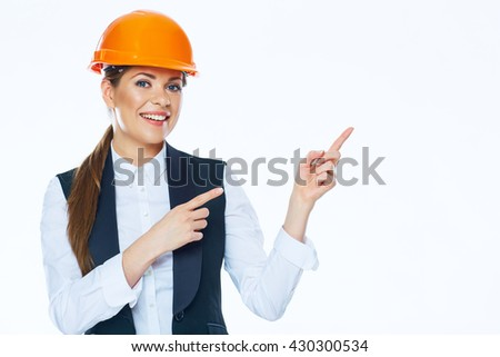 Woman builder in helmet points finger at copy space on white background.  - stock photo