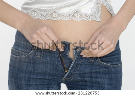 Woman Buttoning Pants