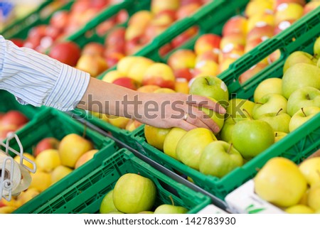 Woman buying a fresh green apple in a supermarket reaching across to remove one from a bin in the display - stock photo