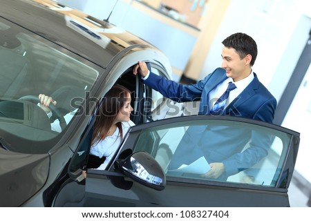 Woman buying a new car - stock photo