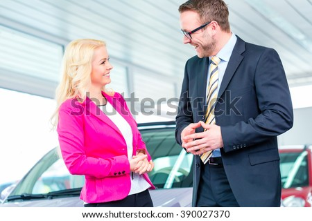 Woman buying car at dealership and consulting salesman - stock photo