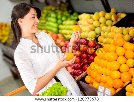 Woman buying fresh fruit at the supermarket - stock photo