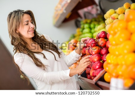 Woman buying fresh fruits at the supermarket - stock photo