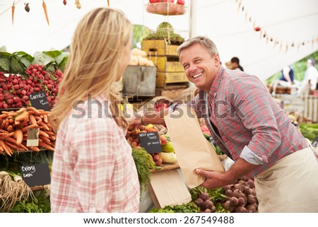 Woman Buying Fresh Vegetables At Farmers Market Stall - stock photo