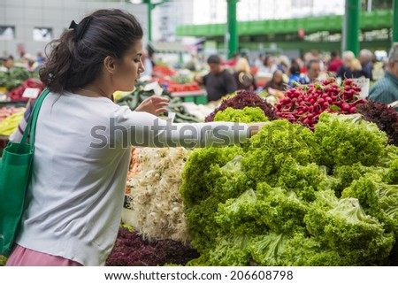 Woman buying fresh vegetables on the market - stock photo