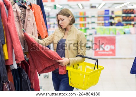 woman buying jacket in shop - stock photo