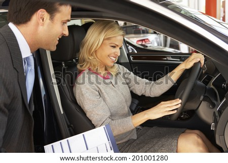 Woman buying new car - stock photo