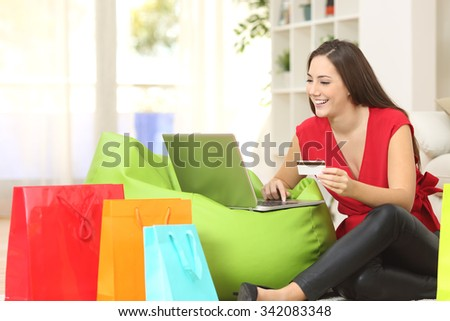Woman buying online at home with a credit card and multiple shopping bags beside - stock photo