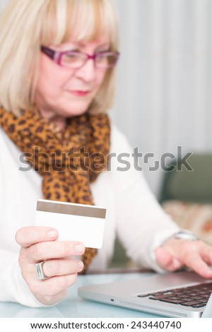 Woman buying online with credit card and showing hand ok sign. Selective focus on hand and credit card