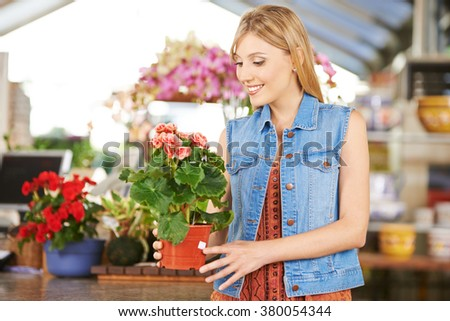 Woman buying pot with begonia in nursery of a garden center - stock photo