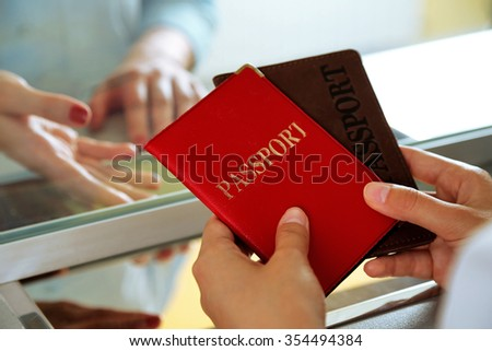 Woman buying tickets with passports at box office - stock photo