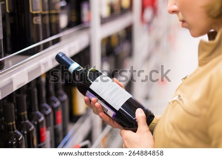 woman buying wine in the supermarket  - stock photo
