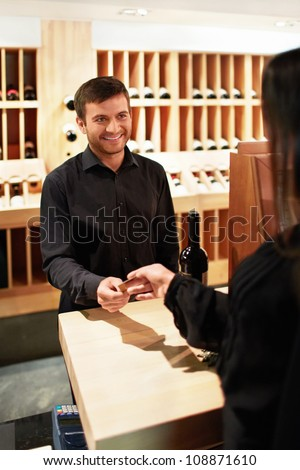 Woman buys a bottle of wine in the store - stock photo