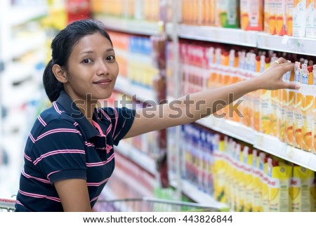 Woman buys a juice in the store. Asian consumer choose food at shelf of the mall. A variety of drinks on offer shop.