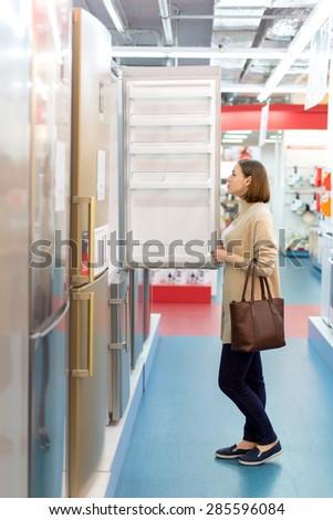 woman buys a refrigerator - stock photo