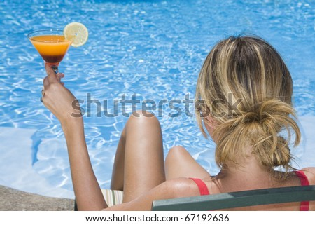 Woman by a blue pool holding a cocktail - stock photo