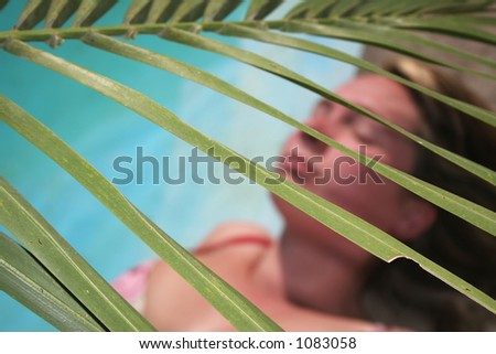 Woman by pool with palm fronds