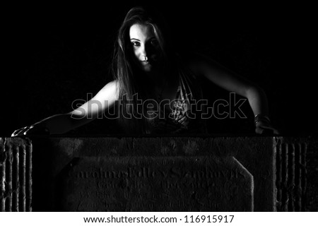 Woman by the grave - Halloween Concept - dramatic lighting