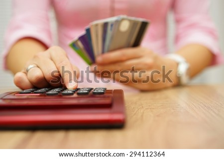 woman calculate how much cost or spending have with credit cards - stock photo