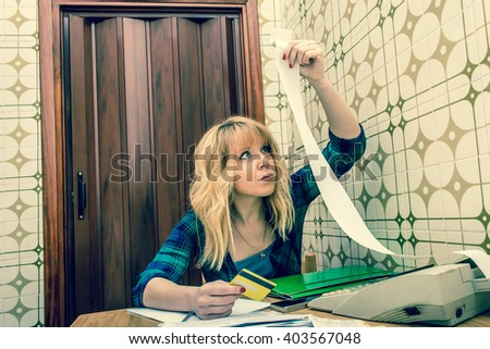 woman calculating home bills and credit card balance at home - lady checking home accounts and financial letters - concept of single life and its high costs - grainy vintage  look filters - stock photo