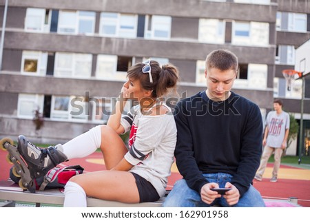 Woman calling during dispute with her boyfriend. They are sitting on the bench. - stock photo