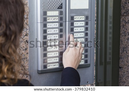 Woman  calling on the intercom and presses the button