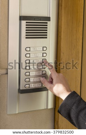 Woman  calling on the intercom and presses the button - stock photo