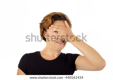 Woman Can't Look Away. Looking Through Hand On Face - stock photo