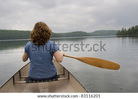 Woman canoeing on a lake - stock photo