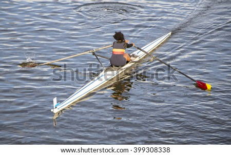 woman canoeist paddling during a race in an Italian lake - stock photo