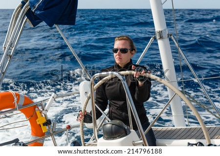 Woman captain at the helm of big cruising yacht - stock photo
