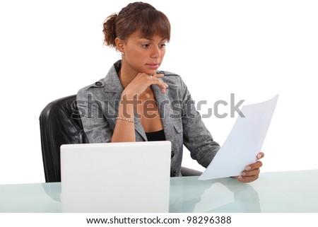 Woman carefully reading through document - stock photo