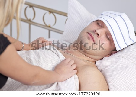 woman caring for sick man on the bed - stock photo