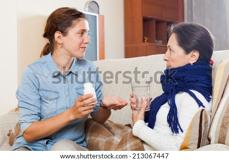 woman caring for sick mature mother in living room at home