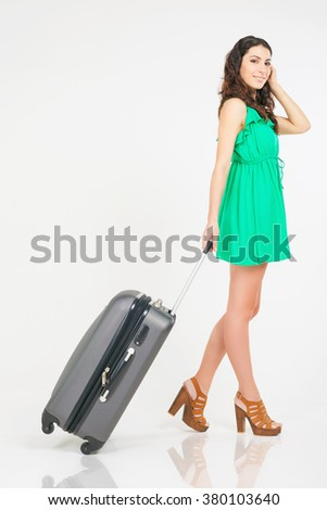 Woman carries your luggage at the airport terminal. Suitcase. Traveler girl dressed in summer green dress. Tourism. Tourist bag. Travel to south of Thailand, Phuket - stock photo