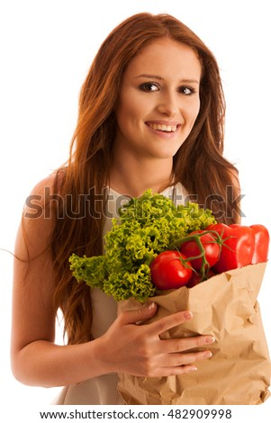 woman carrying a bag full of various vegetables isolated over white background
