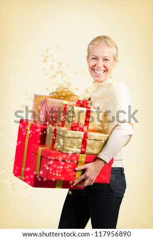 Woman carrying a lot of Christmas presents on yellow background - stock photo