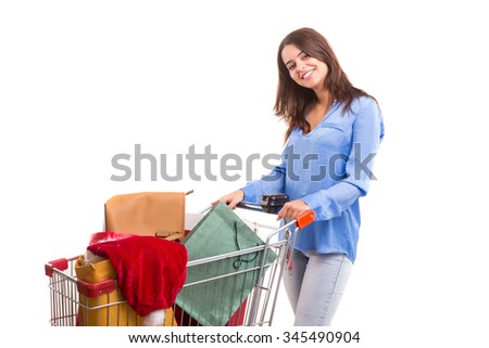 Woman carrying a shopping cart full of gifts - stock photo