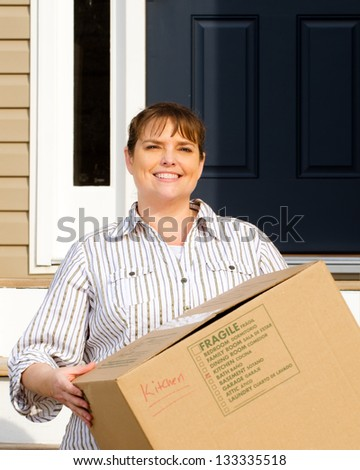 Woman carrying box on moving day in front of home - stock photo