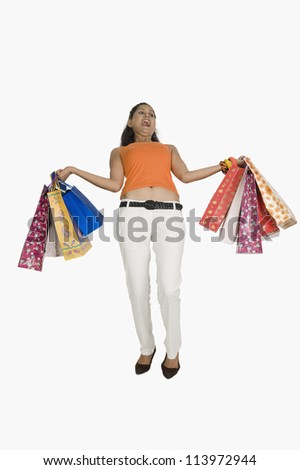 Woman carrying heavy shopping bags - stock photo