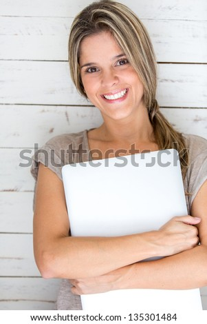 Woman carrying her laptop and looking very happy