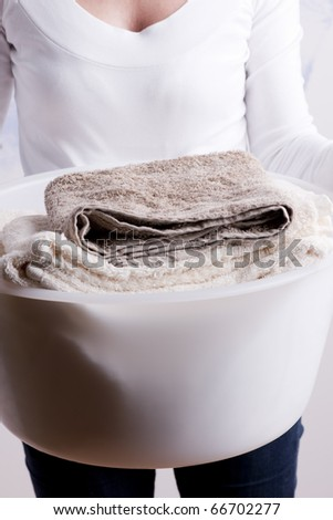 Woman carrying laundry basket - stock photo