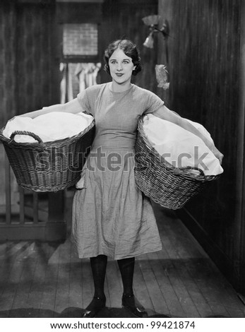 Woman carrying laundry baskets - stock photo