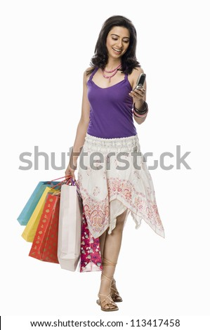 Woman carrying shopping bags and text messaging on the phone - stock photo