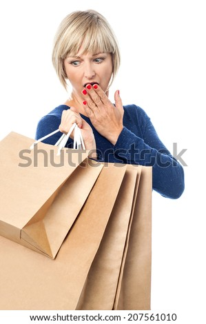 Woman carrying shopping bags, looking back - stock photo