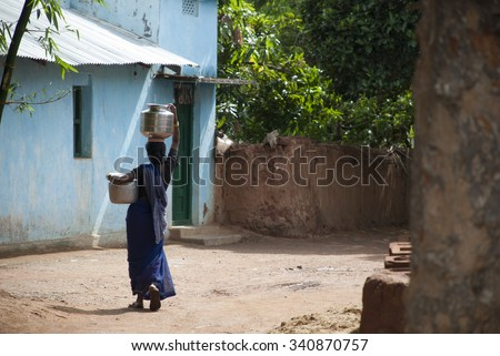 Woman carrying water bucket on head