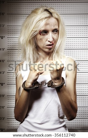 Woman catched in handcuffs in front of mugshot board - stock photo