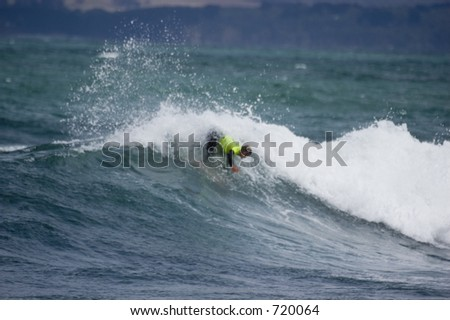 Woman catching a good wave with her surfboard in Australia