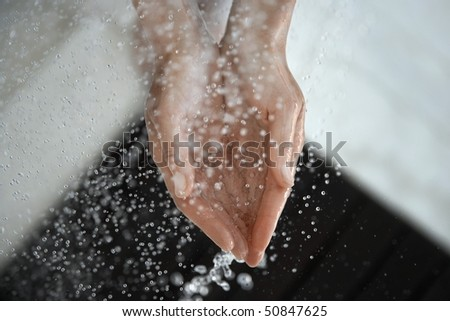 Woman catching water in cupped hands, close up of hands, view from above