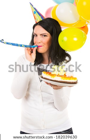 Woman celebrate her birthday with party hat,balloons,cake and blowing into a horn blower  against white background - stock photo